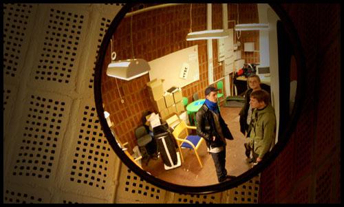 de tre redaktionsmedlemmarna syns i rund spegel med tegelvägg bakom
