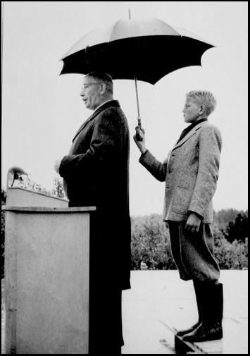 Per Edvin Sköld som talar och Sven Olof Bäckström med paraply bakom